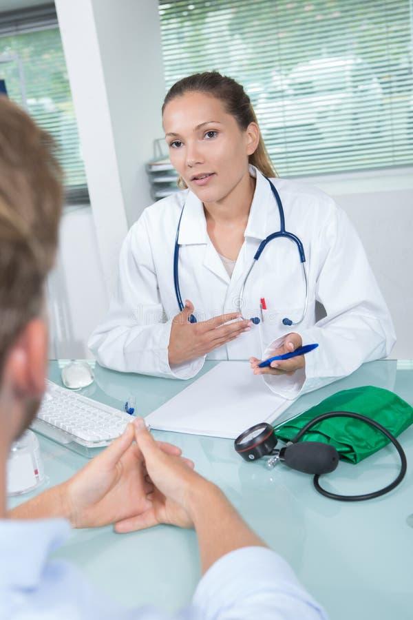 Jeune docteur féminin attirant regardant l'histoire de patients image stock