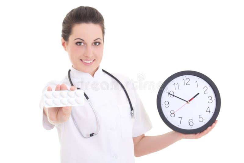Jeune docteur féminin avec des pilules et horloge d'isolement sur le blanc image stock