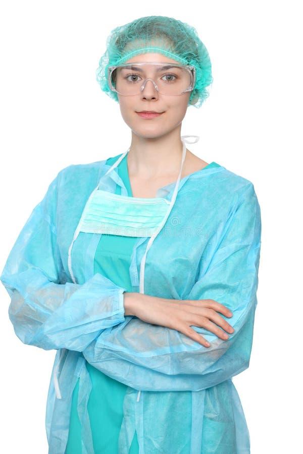 Jeune docteur féminin de chirurgien se tenant avec des bras croisés et souriant, au-dessus du fond blanc photo libre de droits
