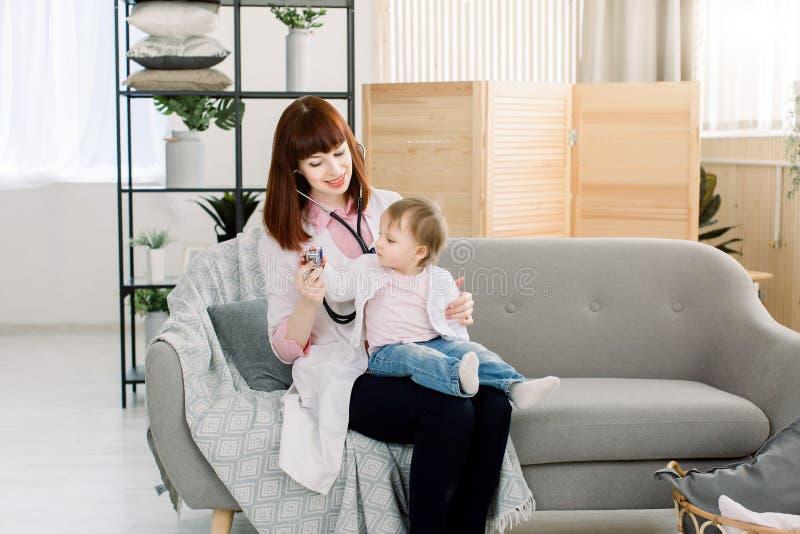 Jeune docteur féminin examinant un petit bébé par le stéthoscope Bébé dans le bureau du docteur pour la visite médicale photo libre de droits