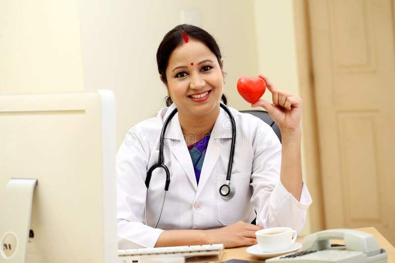 Jeune docteur féminin indien tenant la forme rouge de coeur photographie stock