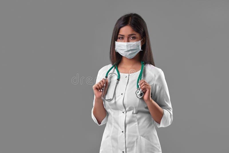 Jeune docteur féminin portant le masque protecteur avec le stéthoscope images stock