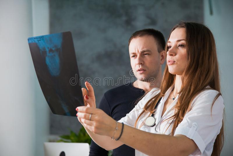 Jeune docteur féminin professionnel montrant le rayon X de l'aviron humain photo stock