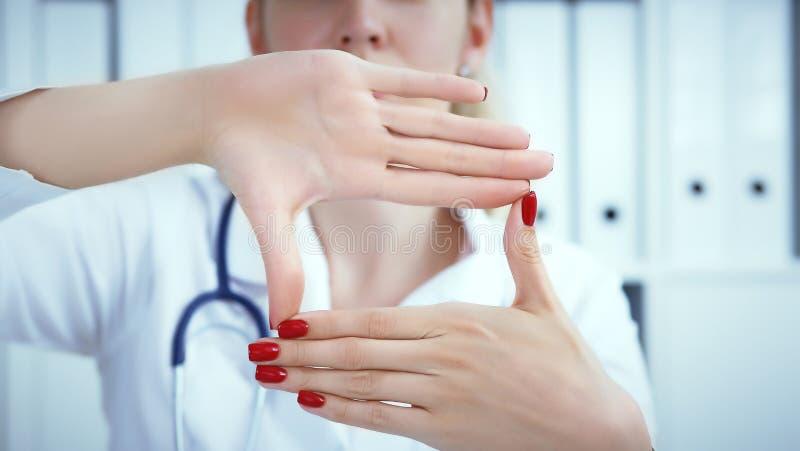 Jeune docteur féminin tenant des mains avec faire de la publicité le secteur entre elles et le sourire sur le bureau médical à l' photographie stock
