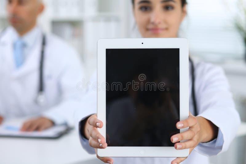 Jeune docteur féminin tenant le pavé tactile ou le comprimé avec l'espace de copie La publicité dans la médecine image stock