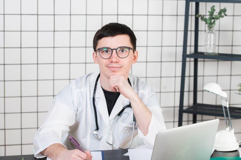 Jeune docteur masculin de sourire travaillant à la réception de clinique, il utilise un ordinateur et rédige des rapports médicau photos libres de droits