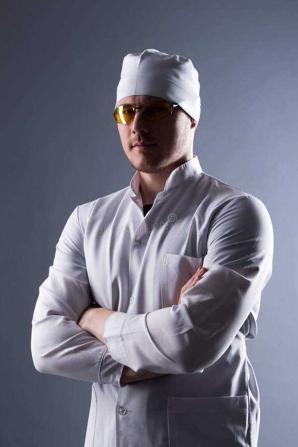 Jeune docteur masculin en chapeau et verres jaunes dans la lumière contrastante image stock