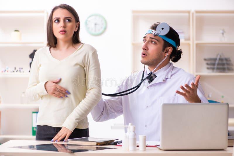 Jeune docteur masculin et beau patient féminin photographie stock
