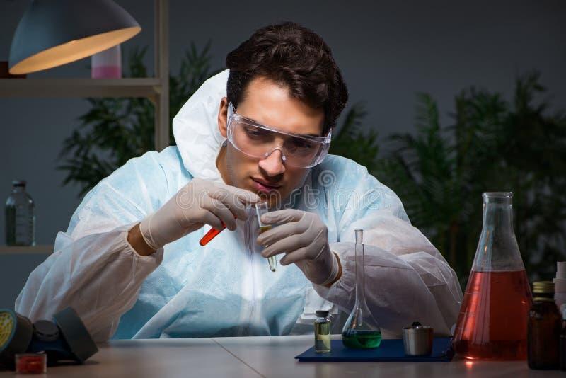 Jeune docteur masculin faisant l'analyse de sang tard la nuit dans les heures supplémentaires Tim photo libre de droits