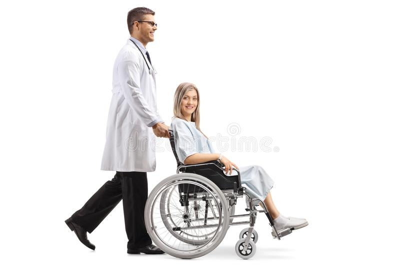 Jeune docteur masculin poussant un patient féminin dans un fauteuil roulant photographie stock libre de droits