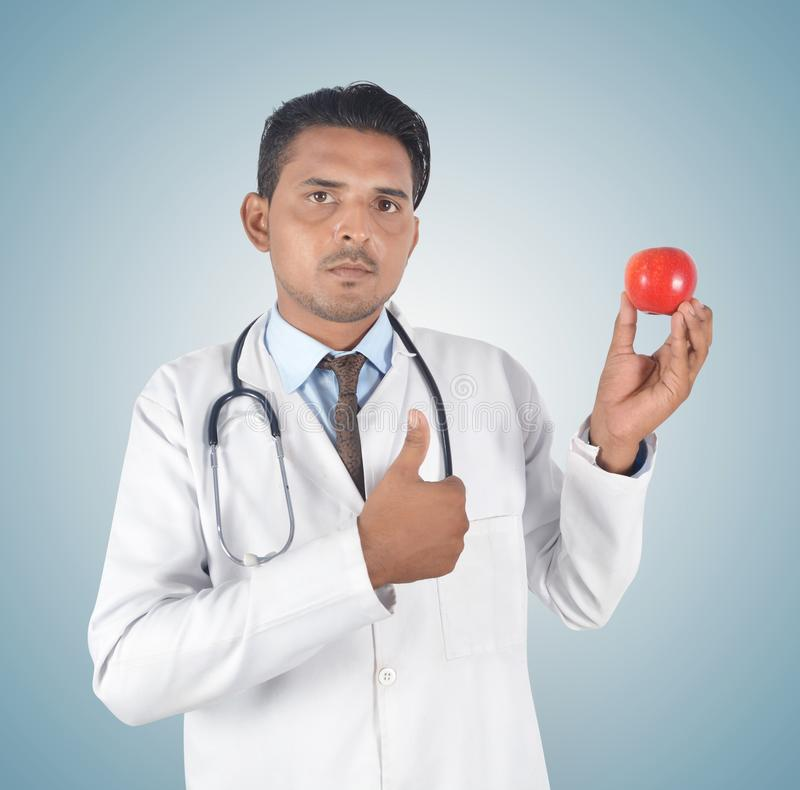 Jeune docteur masculin tenant une pomme et un pouce rouges  photographie stock