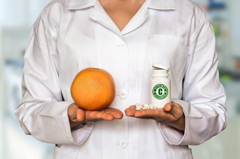 Jeune docteur tenant le pamplemousse et la bouteille de pilules avec la vitamine photos libres de droits