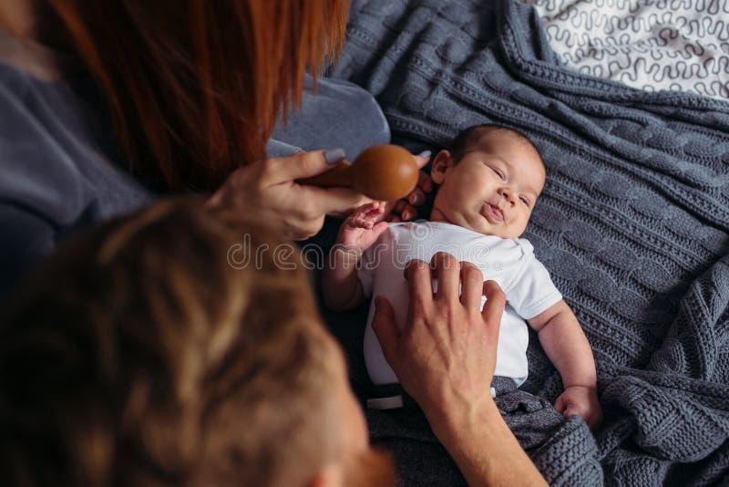 Jeune donner de parents de l'attention à leur bébé images stock