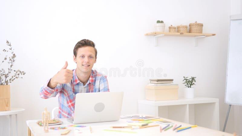 Jeune donner enthousiaste de concepteur des pouces lèvent le signe images libres de droits