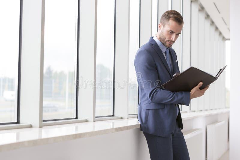 Jeune dossier beau de lecture d'homme d'affaires dans le nouveau bureau images stock
