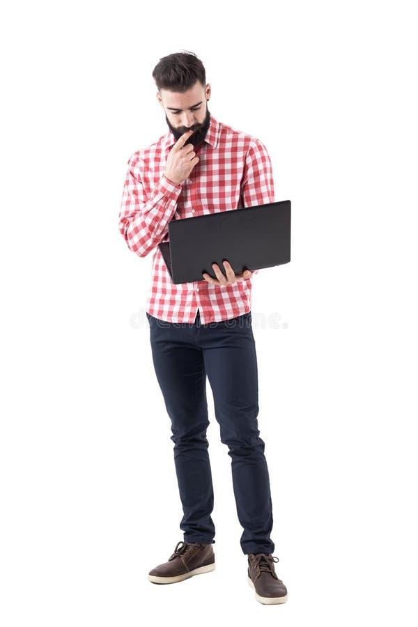 Jeune employé d'homme d'affaires se tenant et travaillant sur l'ordinateur portable photos libres de droits