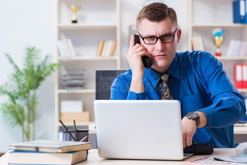 Jeune employé d'homme d'affaires travaillant dans le bureau au bureau photo stock