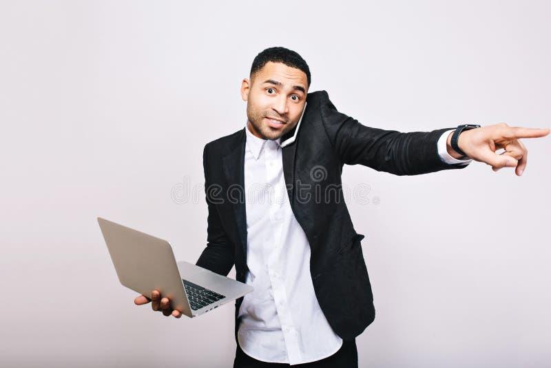 Jeune employé de bureau bel joyeux occupé dans la chemise blanche et l'ordinateur portable noir de participation de veste, parlan photo stock