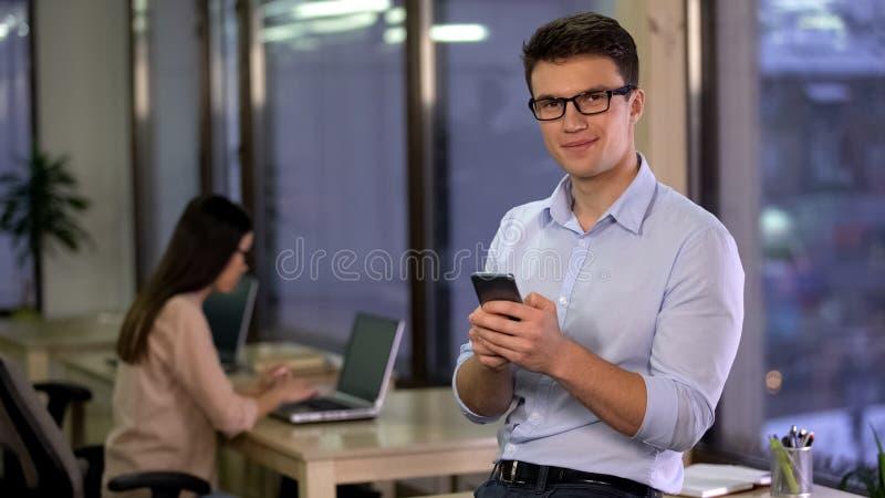 Jeune employ? de bureau bel regardant la cam?ra avec des mains de smartphone, application photographie stock