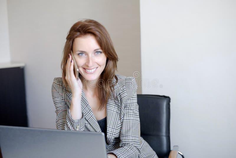 Jeune employé de bureau mignon parlant au téléphone portable dans le bureau images stock