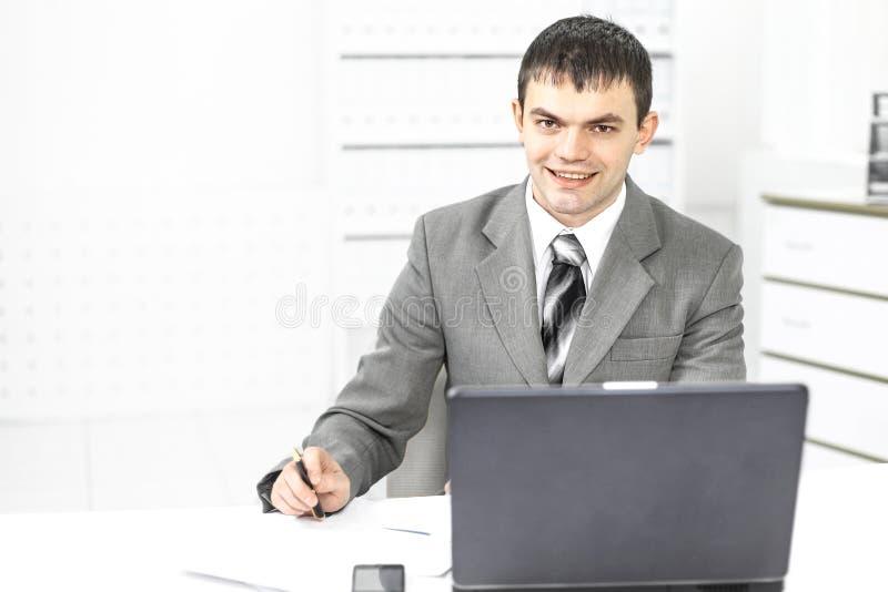 Jeune employ? d'une soci?t? se reposant sur un lieu de travail image stock