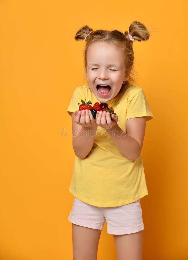 Jeune enfant de bébé avec une poignée de baies dans des ses mains de paumes criant avec bonheur ou dans l'effroi sur le jaune photos stock