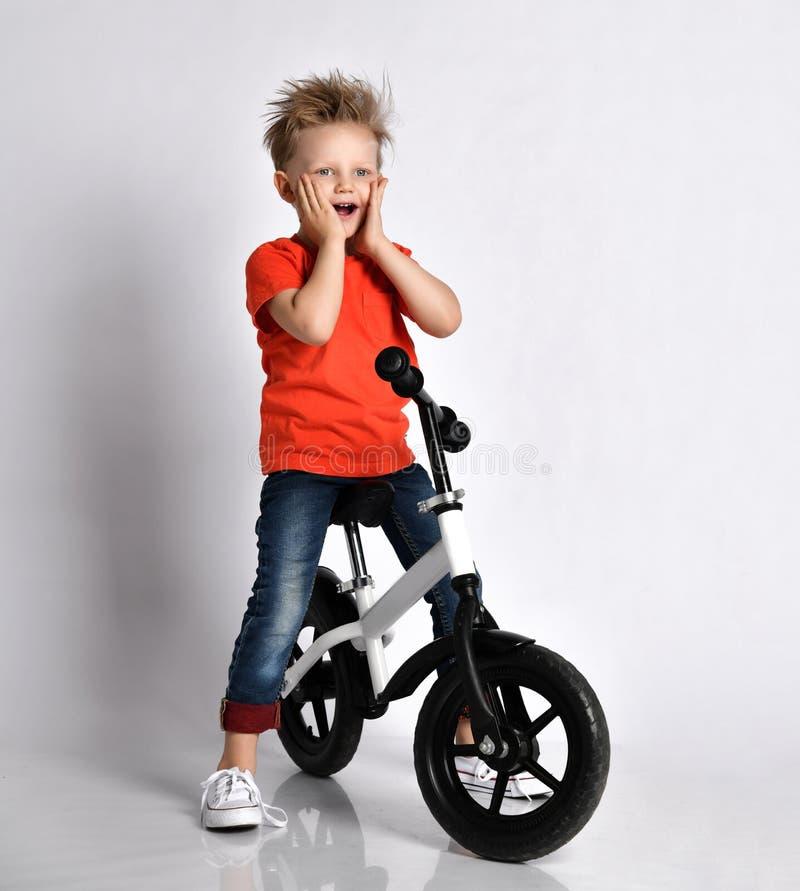 Jeune enfant de garçon dans des cris heureux de T-shirt de cycliste de bicyclette orange de tour photos libres de droits