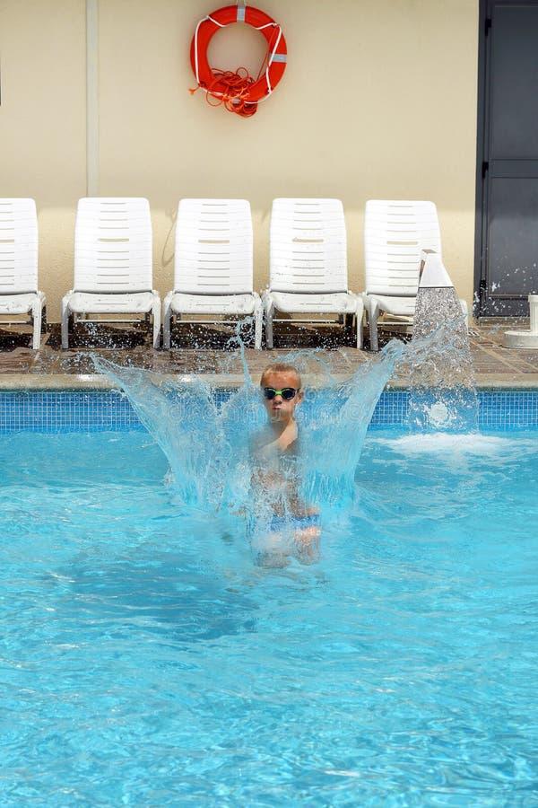 Jeune enfant de garçon sautant dans la piscine photos libres de droits