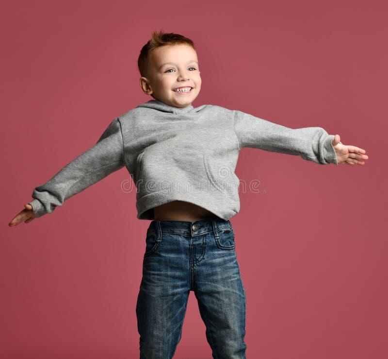 Jeune enfant de garçon sautant dans le hoodie gris avec des mains répandues vers le haut du sourire riant sur le rose images libres de droits