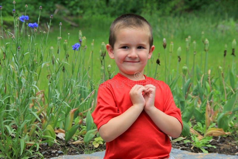 Jeune enfant de sourire faisant le coeur avec de petites mains images libres de droits