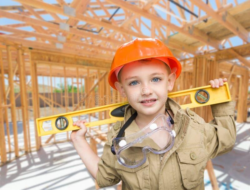 Jeune entrepreneur de garçon avec le niveau sur le site à l'intérieur de nouveau Construc à la maison photographie stock libre de droits