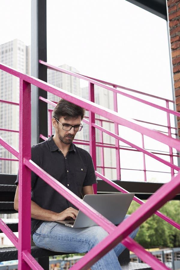 Jeune entrepreneur de type travaillant dehors utilisant l'ordinateur portable moderne se reposant sur des escaliers Concept de dé photos stock