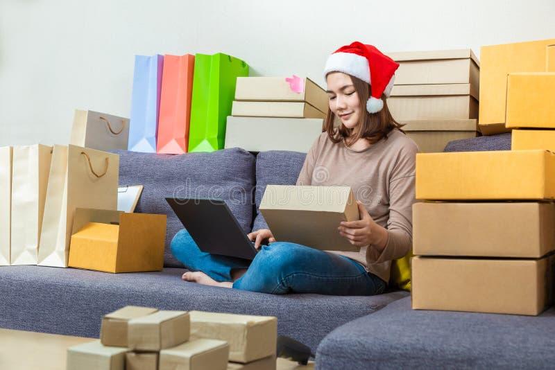 Jeune entrepreneur en ligne féminin asiatique de vendeur, chapeau de port de Noël, travaillant à ses affaires en ligne images libres de droits