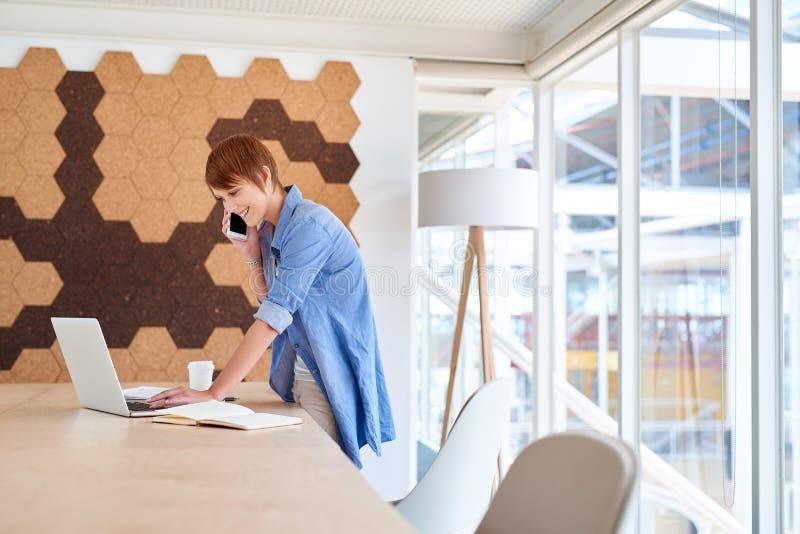 Jeune entrepreneur féminin semblant occasionnel dans un spac moderne de bureau photos libres de droits