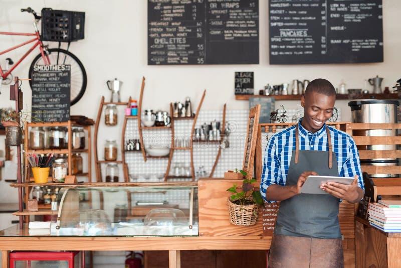 Jeune entrepreneur se tenant en son café utilisant un comprimé numérique images libres de droits