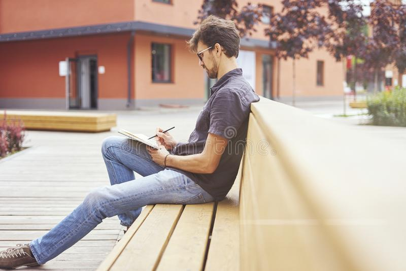 Jeune entrepreneur travaillant au parc dehors sur le banc en bois Verres de port d'homme bel utilisant le livre, écrivant le text photo stock