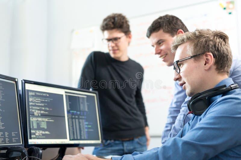 Jeune entreprise, programmateur de logiciel travaillant sur l'ordinateur de bureau images stock