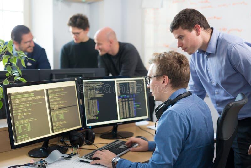 Jeune entreprise, programmateur de logiciel travaillant sur l'ordinateur de bureau photographie stock libre de droits