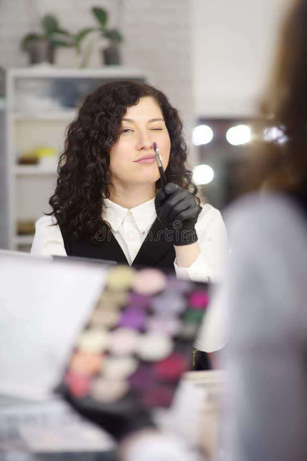 Jeune esthéticien ayant l'amusement pendant le travail dans un salon de beauté photographie stock libre de droits