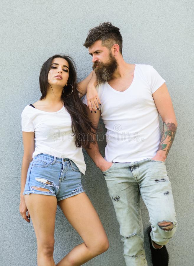 Jeune et élégant Les chemises blanches de couples caressent près du mur gris Coup à la mode brutal de hippie et élégant barbu de  images libres de droits