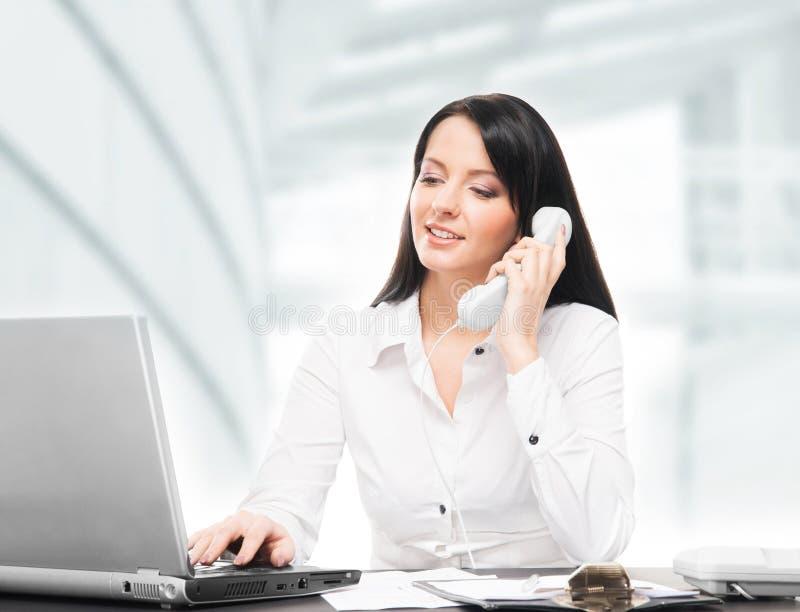 Jeune et attirante femme d'affaires parlant au téléphone image stock