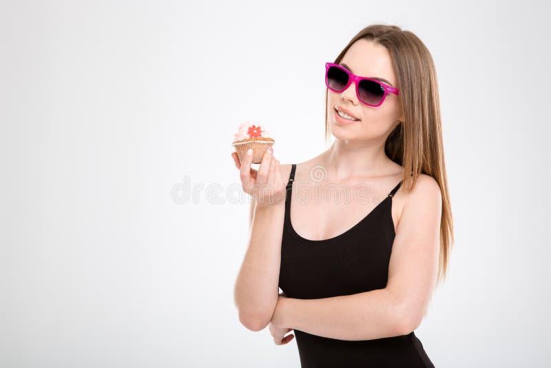 Jeune et attirante fille tenant un petit gâteau dans des ses mains photos libres de droits