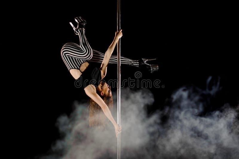 Jeune et belle danse de poteau d'exercices de femme dans la fumée sur un fond noir images libres de droits