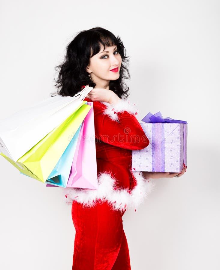 Jeune et belle femme dans le manteau rouge tenant une boîte intéressante et des paniers de cadeau de Noël photographie stock