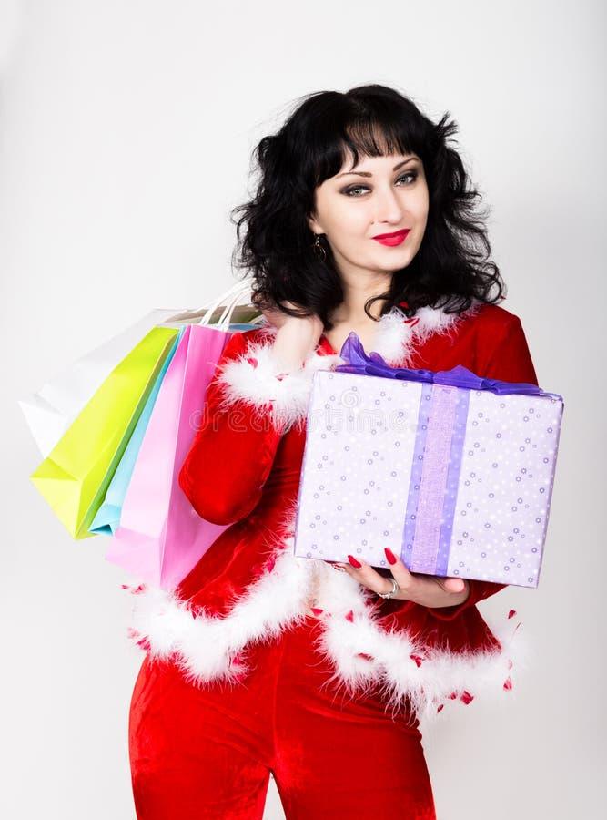 Jeune et belle femme dans le manteau rouge tenant une boîte intéressante et des paniers de cadeau de Noël photos libres de droits