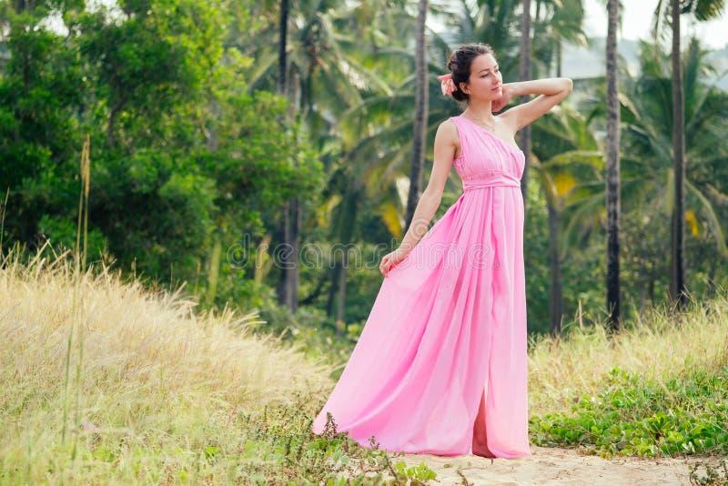Jeune et belle femme posant dans une élégante robe de luxe rose et chic sur fond de palmiers. Concept photos stock