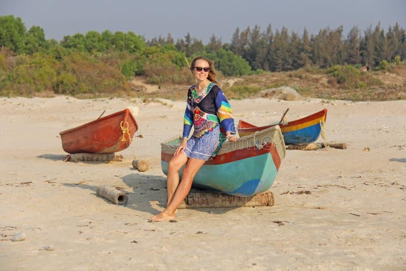 Jeune et belle fille dans des lunettes de soleil, avec les cheveux blonds, se reposant sur un bateau, souriant sur la plage et re photo libre de droits