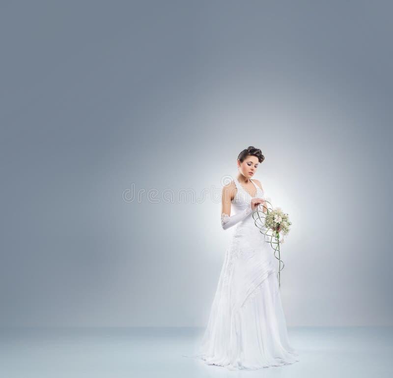 Jeune et belle jeune mariée dans une longue robe d'imagination photos libres de droits