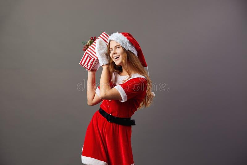 Jeune et belle Mme Claus s'est habillé dans la robe longue rouge, le chapeau de Santa et les gants blancs tient le cadeau de Noël photos libres de droits