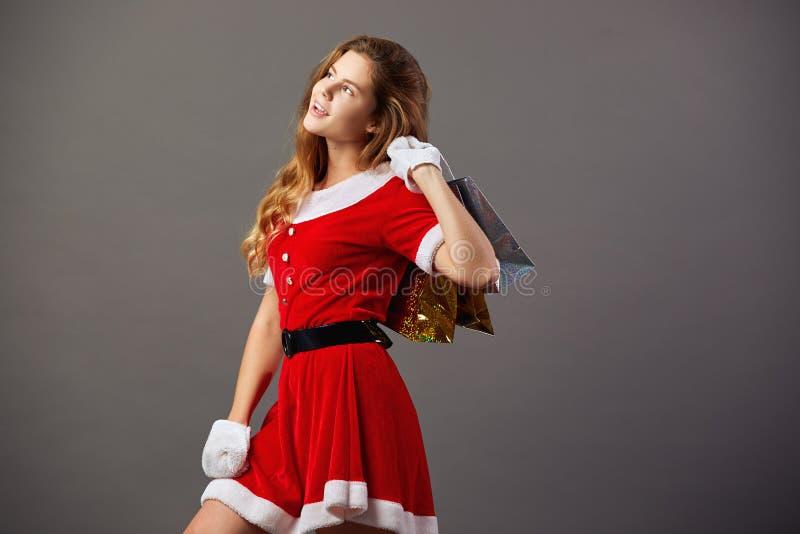 Jeune et belle Mme Santa Claus dans des lunettes de soleil habillées dans la robe longue rouge et les gants blancs tient les sacs photos libres de droits